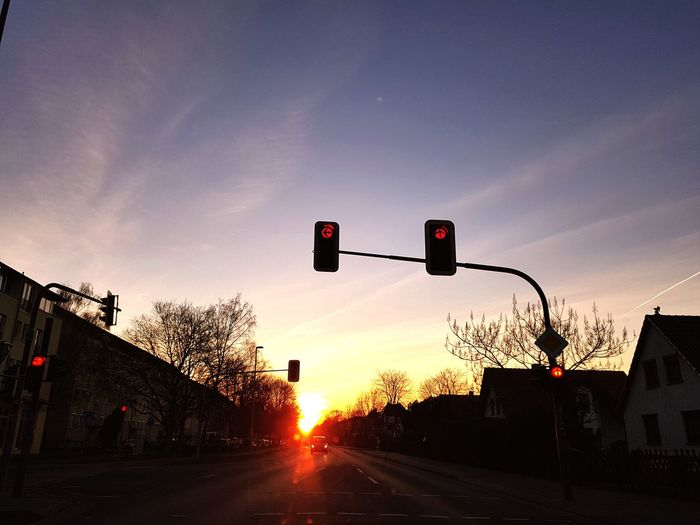 Road signal against sky during sunset