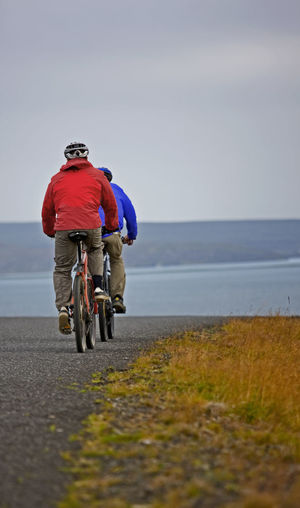 Rear view of man riding bicycle on beach