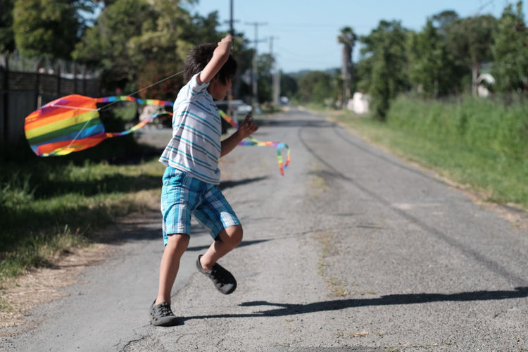 Full Length Of Boy Playing With Kite On Road Against Sky