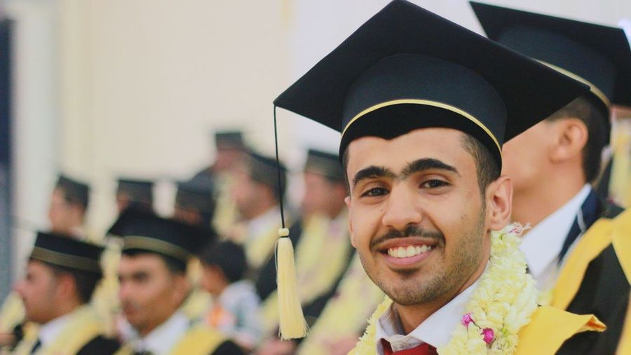 Portrait Of Smiling Young Man Wearing Graduation Gown Standing With Students