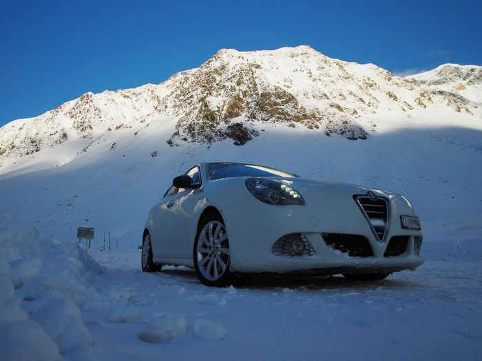 Alfa Romeo Giulietta Quadrifoglio Verde on a snow covered mountain road Beauty In Nature Blue Car Cold Temperature Day Mountain Nature No People Outdoors Sky Snow Winter The Drive The Drive.