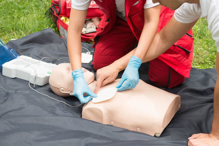Man instructing while paramedic practicing cpr on dummy