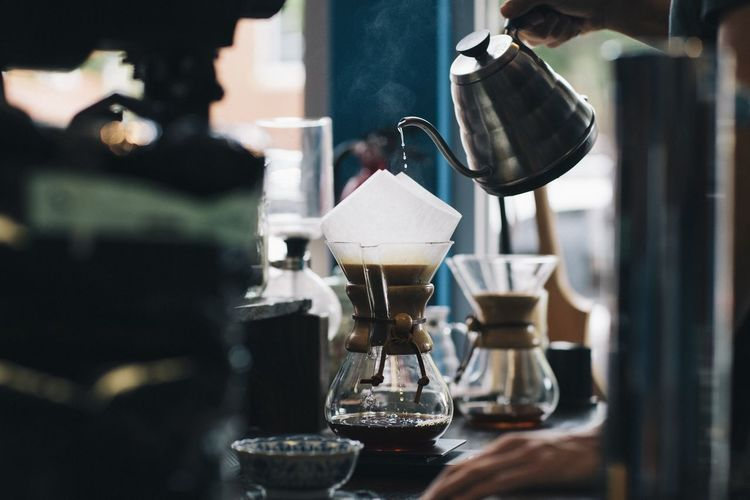 Close-up of hand pouring coffee in cafe