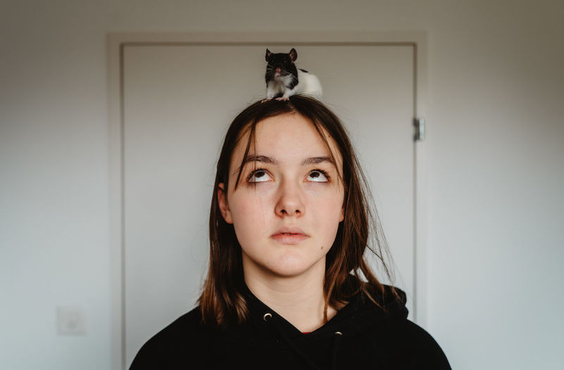 Portrait of young woman against wall at home