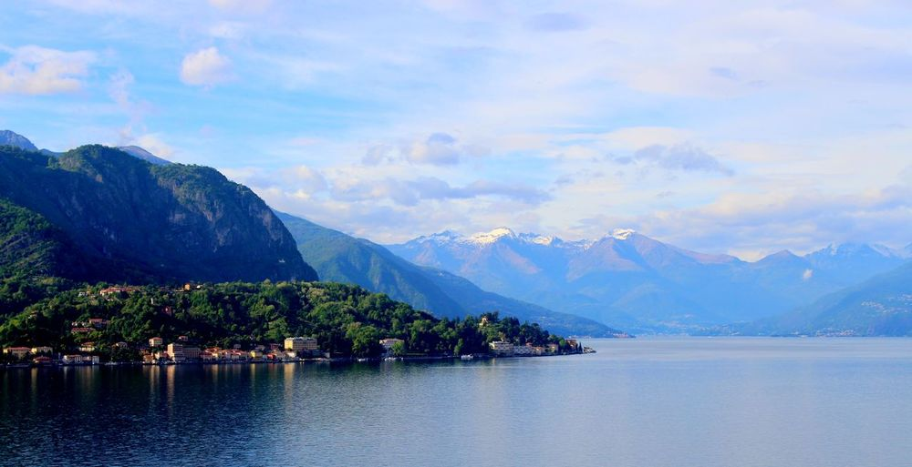 Scenic view of lake como and mountains against cloudy sky