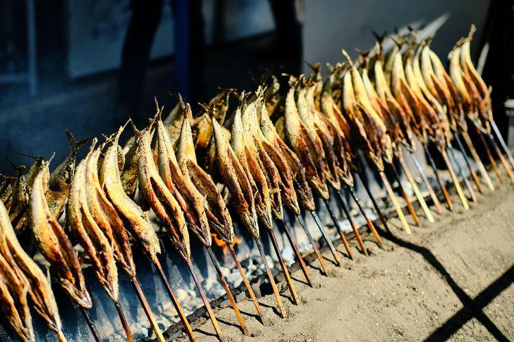 Line of barbequed fish on sticks at front of street food vendor