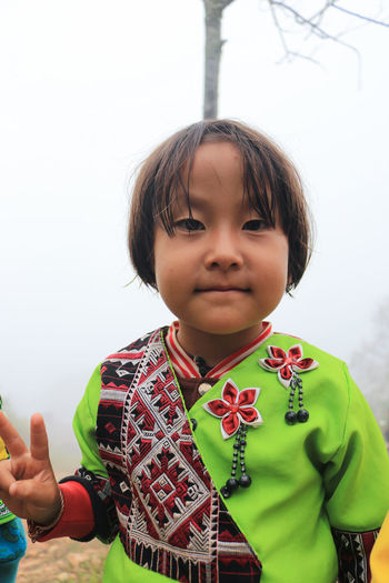 Portrait of girl in traditional clothing standing against sky
