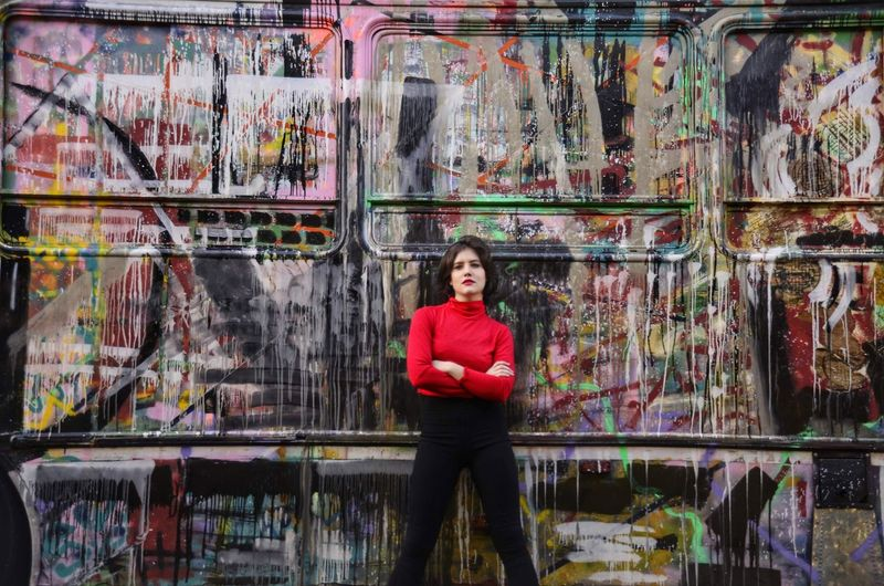 Portrait of young woman standing against graffiti wall