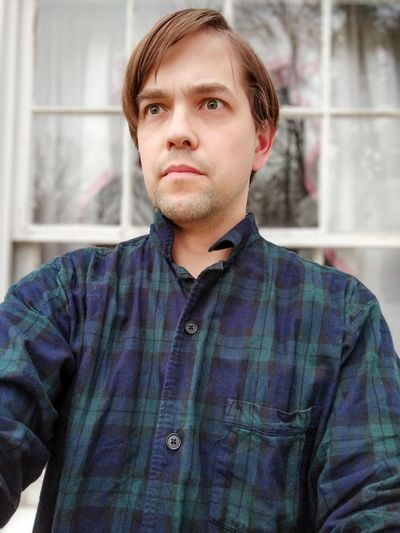 Portrait of man with worried or concerned expression in front of window