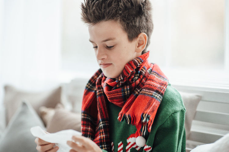 Close-up of boy looking at tissue paper sitting at home