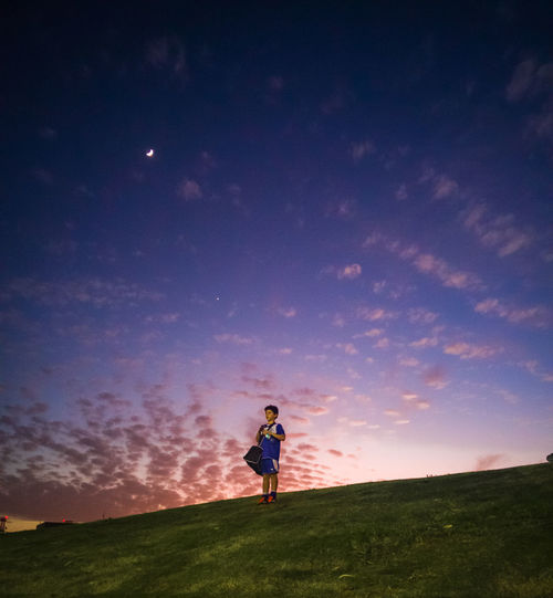 Boy In Sports Clothing On Hill At Sunset