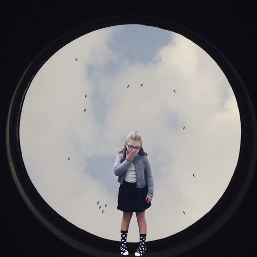 Digital composite image of surprised girl covering mouth standing on sky light against sky