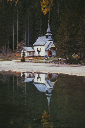 Built structure by lake against trees and house in forest