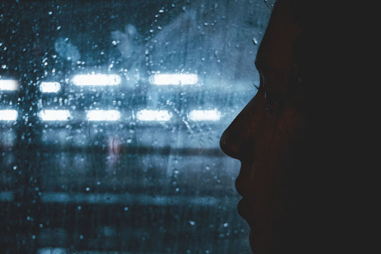 Close-Up Of Silhouette Woman Looking Through Window At Night During Rainy Season