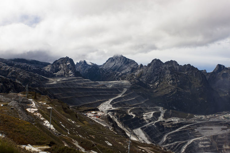 Scenic view of mountains above grasberg mine road against cloudy sky