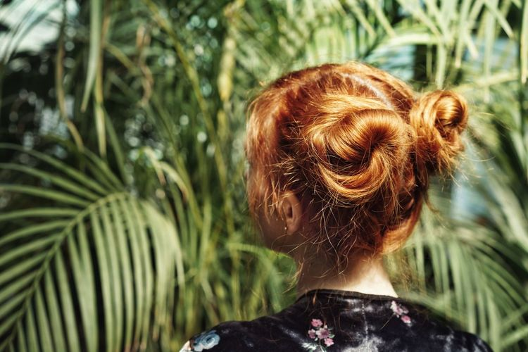 Rear view of woman with hair buns against palm tree