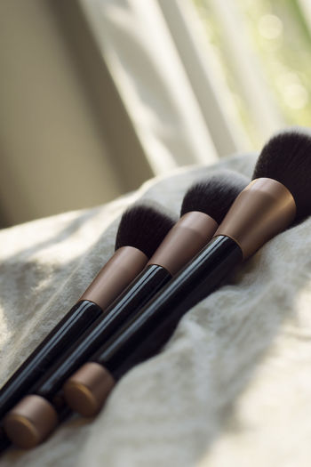 Three makeup brushes on bed Foundation Make-up Makeup Accessories Beauty Bed Brush Brushes Close-up Day Indoors  Lifestyles Make-up Brush Makeupartist Pretty Relaxation Selective Focus Simple