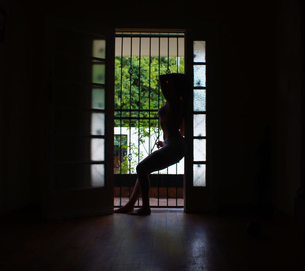 Side view of silhouette woman standing by window at home