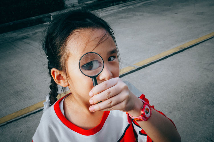 Portrait One Person Headshot Real People Looking At Camera Lifestyles Holding Glasses Eyeglasses  High Angle View Child Front View Childhood Street Outdoors Day Innocence Hairstyle Girls Leisure Activity Women Teenager