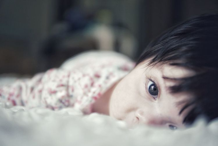 Close-up of cute baby girl lying down on bed