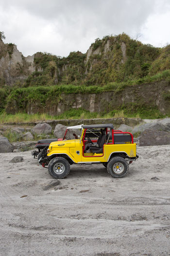 Parked 4 x 4 vehicle in rough terrain. 4 X 4 Adventure Beauty In Nature Day Land Vehicle Landscape Mode Of Transport Mountain Nature Non-urban Scene Off-Road Outdoors Parked Parking Road Rough Stationary Terrain Transportation Vehicle Yellow