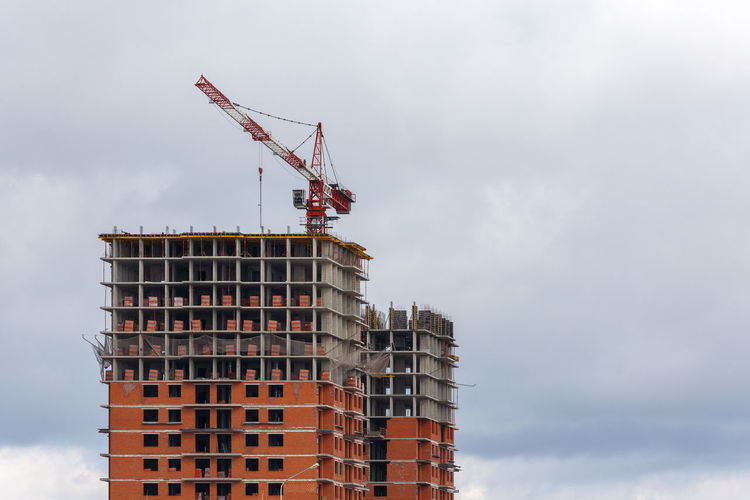 Building process of large residential apartment building with crane on cloudy sky background