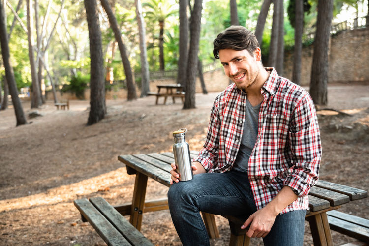 Portrait of smiling young man holding drink container while sitting on bench