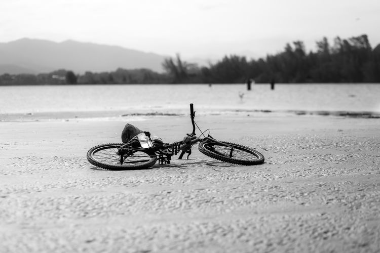 Man riding bicycle by lake against sky