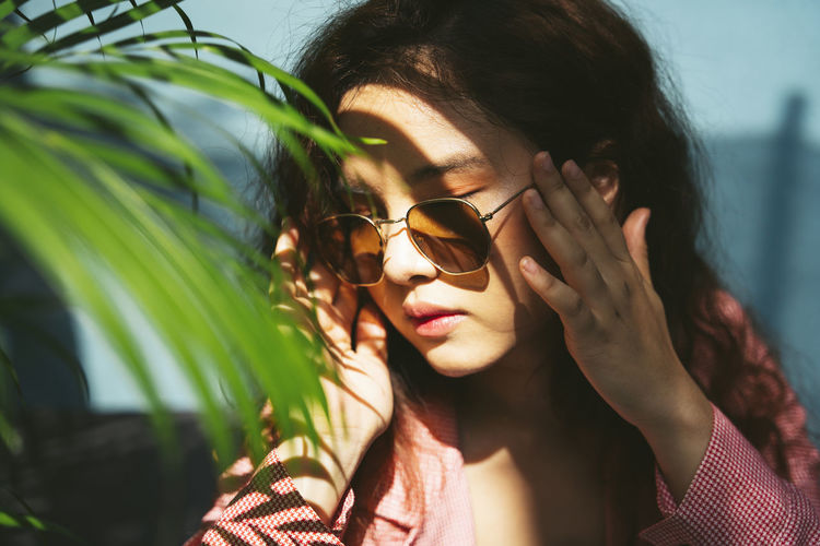 Close-up of woman wearing sunglasses sitting by plants