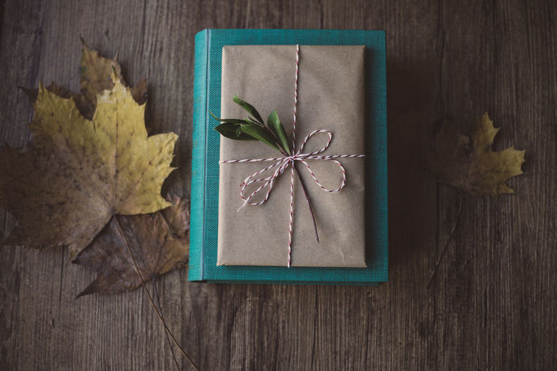 Wrapped gifts on wooden table Book Present Green Wooden Birthday Christmas Holiday Love Wrap Chritsmas Decoration Gift Paper Wrapped Leaf Wood - Material Table Directly Above Anise Food Indoors  No People Close-up Nature Freshness High Angle View Day Flower Dried Plant Flower Head