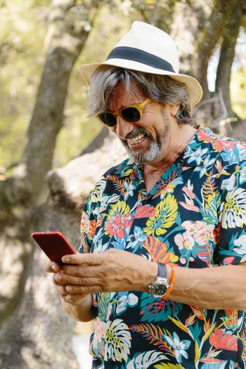 Full length of senior woman using smart phone outdoors