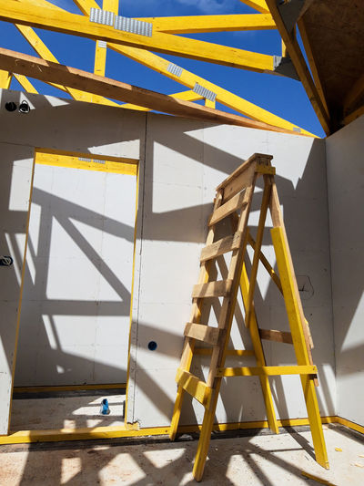 Low angle view of ladder against yellow wall