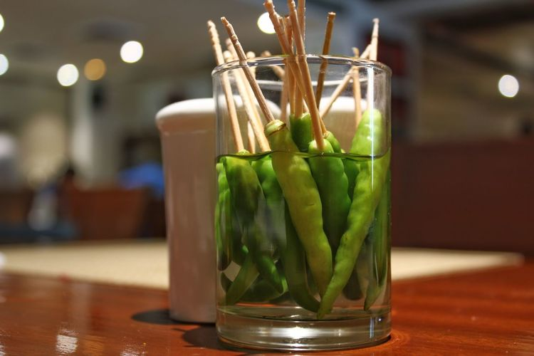 Green chili sticks soaked in vinegar in a glass and kept on a wooden table Chilis Close-up Day Drink Focus On Foreground Food And Drink Glass Green Chili Pepper Green Chillies Green Color Indoors  No People Table Vinegar Wooden Wooden Table EyeEmNewHere