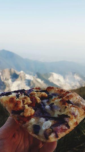 Close-up of hand holding ice cream against mountain range