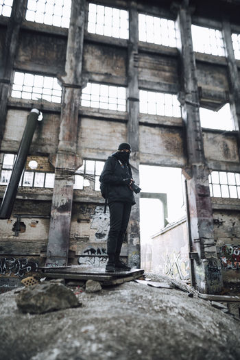 Full length of woman standing on window of abandoned building