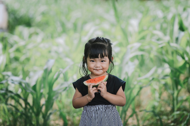 Portrait of smiling girl holding watermelon