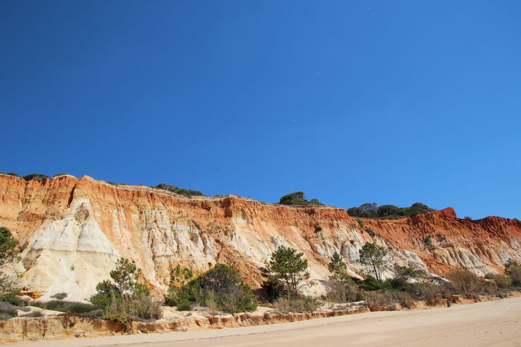 "Ocher, red and yellow, the cliffs shimmer on the long beach of ""Praia da Falesia"" in Portugal on the Algarve. Sky Land Beauty In Nature Blue Scenics - Nature Tranquil Scene Tranquility Nature Day Mountain Non-urban Scene Rock No People Rock Formation Outdoors Praia Da Falésia Algarve Algarve, Portugal Portugal Cliffs Beach Landscape_Collection Landscape_photography Beauty In Nature Landscape"