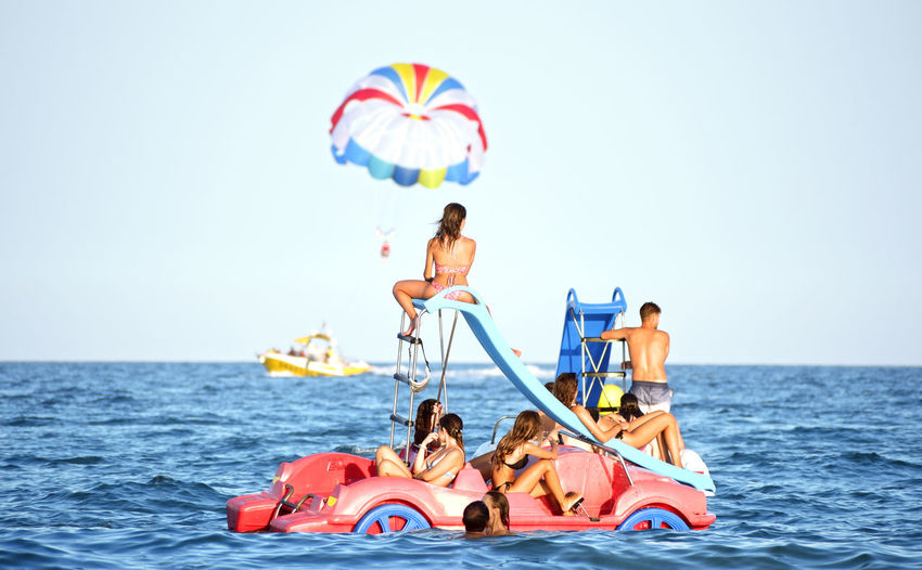 People sitting in sea against sky