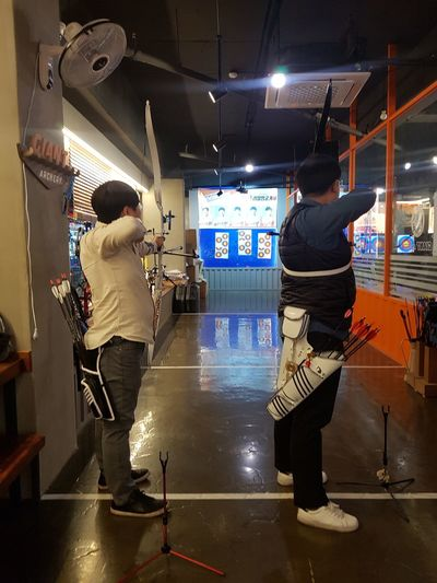 Competition Archery Real People Illuminated Night Lifestyles Full Length Architecture Leisure Activity Indoors