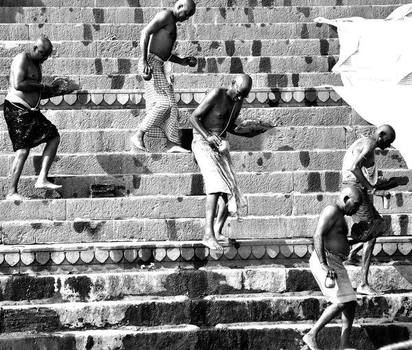 Shirtless men walking on steps