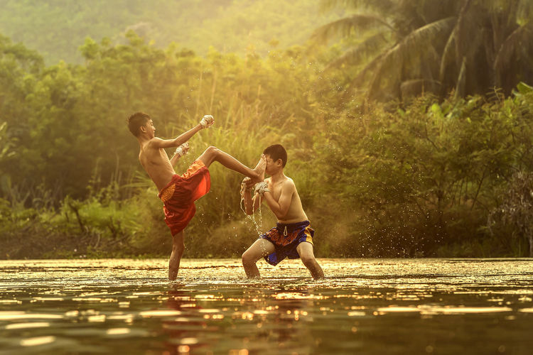 Shirtless boys playing in swamp