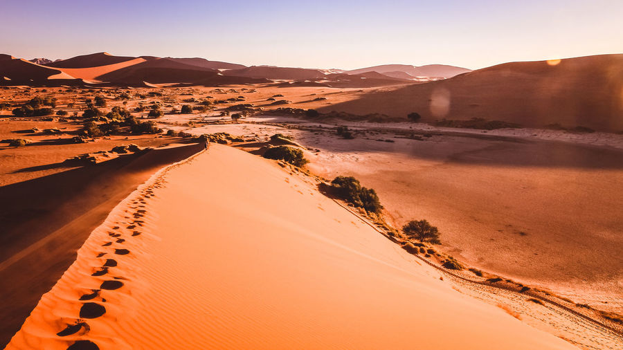 Sossusvlei, Namibia The Great Outdoors - 2018 EyeEm Awards The Traveler - 2018 EyeEm Awards Arid Climate Beauty In Nature Clear Sky Day Desert EyeEm Nature Lover Footsteps Landscape Mountain Namibia Nature Nature Nature Photography Nature_collection Orange Color Outdoors Sand Sand Dune Scenics Sunlight Sunset Perspectives On Nature Tranquility