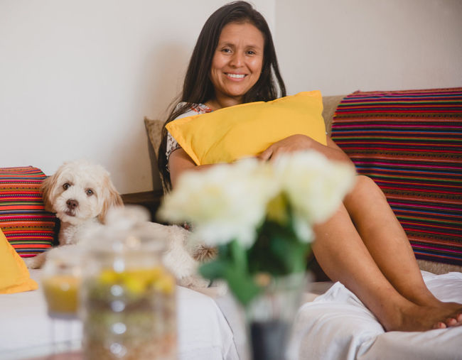Portrait of woman with dog at home