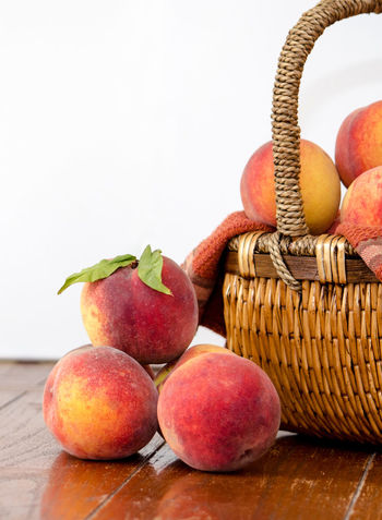 sweet juicy Michigan peaches on a white background Agriculture Fall Colors Freshness Nature Still Life Photography USA Basket Container Food Food And Drink Freshness Fruit Healthy Eating Indoors  Juicy Fruit Just Picked Michigan Peaches Orange Color Organic Peanuts Peach Still Life Table Wellbeing Wood - Material Yellow