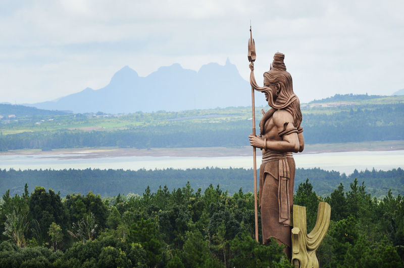 Shiva statue by trees against river