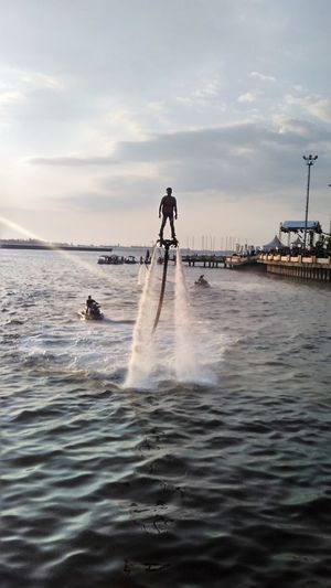 Rear view of man surfing in sea against sky