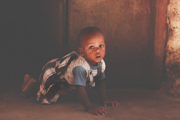 Full Length Portrait Of Baby Boy Crawling By Door