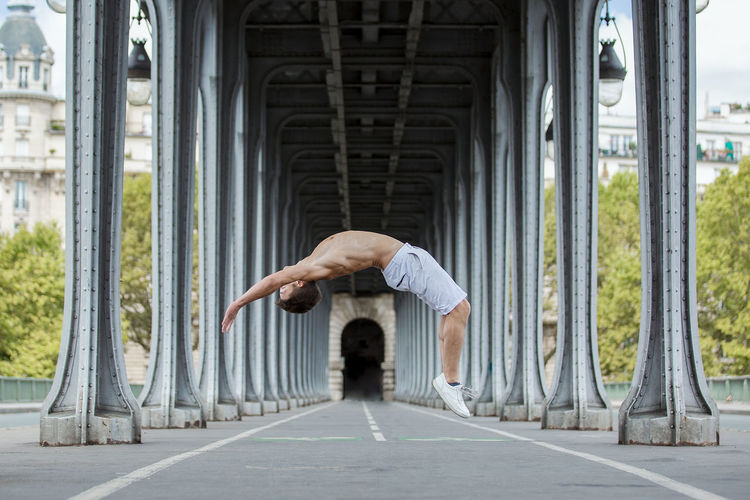 Side View Full Length Of Shirtless Man Jumping Below Bridge