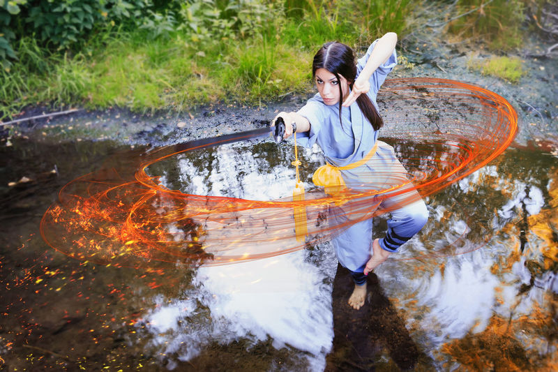Young woman practicing kung fu with sword while standing on puddle in forest
