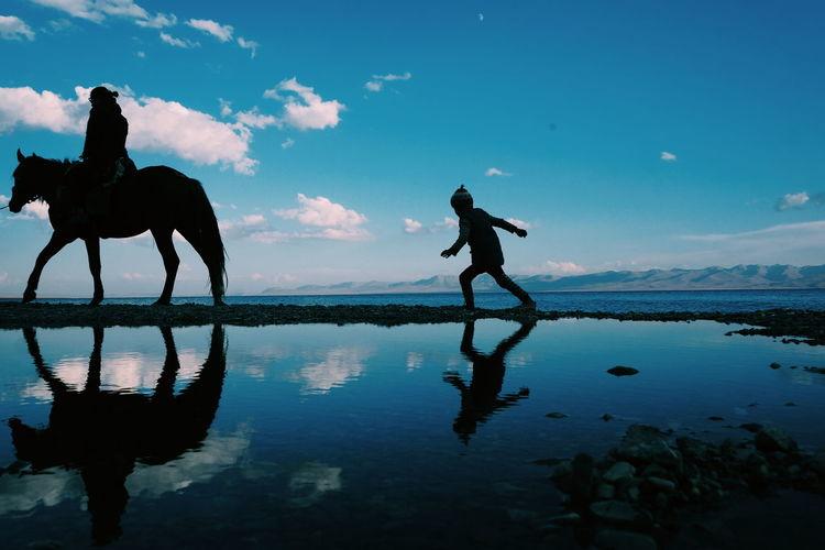 Boy following man riding horse by song kol lake against blue sky